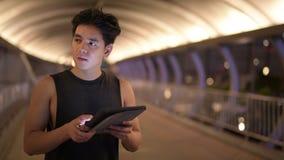 Retrato del hombre asiático hermoso joven que piensa mientras que usa la tableta digital al aire libre en la noche almacen de video
