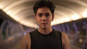 Retrato del hombre asiático hermoso joven que sonríe al aire libre en la noche almacen de video