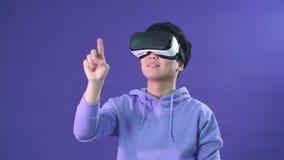 Retrato del hombre asiático joven que juega al juego de VR en fondo azul marino almacen de video