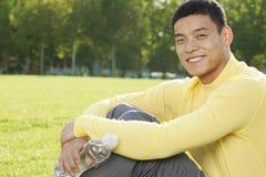 Retrato del hombre atlético joven sonriente que se sienta en la hierba en un parque en Pekín, mirando la cámara Foto de archivo
