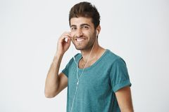 Retrato del hombre atractivo, apuesto, elegante que sonríe a los auriculares blancos que llevan de la cámara El escuchar el nuevo fotografía de archivo libre de regalías