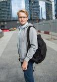 Retrato del hombre atractivo joven con una mochila en la calle cerca del centro de negocios moderno Fotografía de archivo