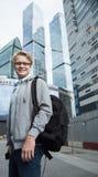 Retrato del hombre atractivo joven con una mochila en la calle cerca del centro de negocios moderno Foto de archivo libre de regalías
