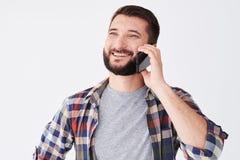 Retrato del hombre barbudo alegre que se coloca y que habla en móvil Foto de archivo libre de regalías