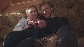Retrato del hombre barbudo hermoso en los vidrios y la mujer bonita que mienten en el heno en el granero frío del invierno Granje metrajes