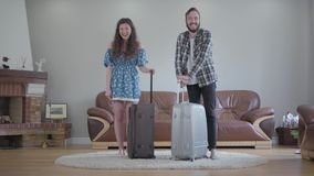 Retrato del hombre barbudo joven en una camisa de tela escocesa y una muchacha hermosa joven listas para el viaje metrajes