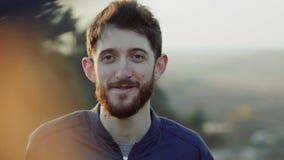 Retrato del hombre barbudo, modesto que mira en su muchacha y que sonríe en la naturaleza almacen de video