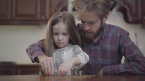 Retrato del hombre barbudo que se sienta en la tabla en la cocina con su hija que cuenta el dinero Beardie en camisa a cuadros metrajes