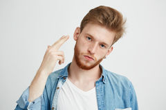 Retrato del hombre brutal joven con la barba que mira la cámara que hace el arma de la mano sobre el fondo blanco Fotografía de archivo