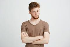 Retrato del hombre brutal joven con la barba que mira la cámara con los brazos cruzados sobre el fondo blanco Fotografía de archivo