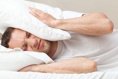 Retrato del hombre caucásico descontento en cama Fotografía de archivo
