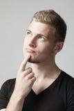 Retrato del hombre caucásico joven pensativo aislado en gris Fotografía de archivo libre de regalías