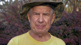 Retrato del hombre caucásico mayor en un sombrero en la calle en la mirada de la cámara metrajes