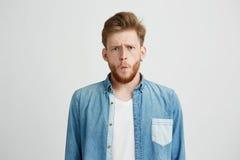 Retrato del hombre chocado emotivo joven que frunce el ceño mirando la cámara sobre el fondo blanco Foto de archivo