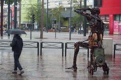 Retrato del hombre con el paraguas en lugar de los adoquines con la estatua metálica en la ciudad Imagen de archivo libre de regalías