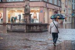 Retrato del hombre con el paraguas en lugar de los adoquines con la fuente en la ciudad Imagen de archivo