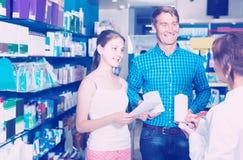 Retrato del hombre con la medicina de las compras del adolescente de la hija en droga Foto de archivo libre de regalías