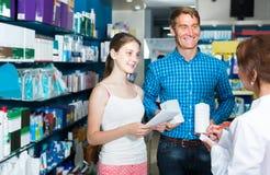 Retrato del hombre con la medicina de las compras del adolescente de la hija en droga Imagenes de archivo