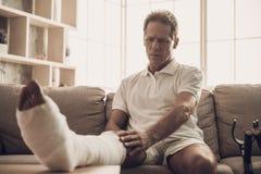 Retrato del hombre con la pierna fracturada que se sienta en el sofá imagen de archivo libre de regalías