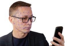 Retrato del hombre con smartphone usando sistema de reconocimiento de la identificación de la cara imagenes de archivo