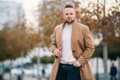 Retrato del hombre confiado en capa marrón y el suéter blanco imagen de archivo