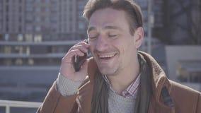 Retrato del hombre confiado hermoso acertado en la situación marrón de la capa en la calle de la ciudad que habla por el teléfono almacen de metraje de vídeo
