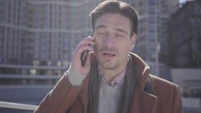 Retrato del hombre confiado hermoso en la situación marrón de la capa en la calle de la ciudad que habla por el teléfono celular  almacen de metraje de vídeo
