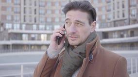 Retrato del hombre confiado hermoso en la situación marrón de la capa en la calle de la ciudad que habla por el teléfono móvil Pa almacen de video