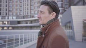 Retrato del hombre confiado hermoso en la situación marrón de la capa en la calle de la ciudad que mira alrededor Paisaje urbano  almacen de metraje de vídeo