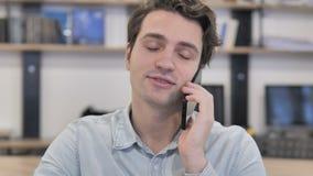 Retrato del hombre creativo que habla en el teléfono en oficina almacen de metraje de vídeo
