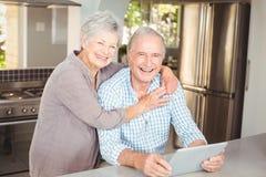 Retrato del hombre de abarcamiento de la mujer mayor feliz con la tableta Foto de archivo libre de regalías
