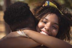 Retrato del hombre de abarcamiento sonriente de la mujer mientras que se coloca en campo Fotos de archivo libres de regalías