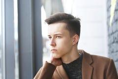 Retrato del hombre de la moda de los jóvenes con la mano en cara Foto de archivo