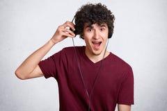 Retrato del hombre de moda hermoso con poca barba, música que escucha de la camiseta marrón casual que lleva en auriculares, teni fotos de archivo