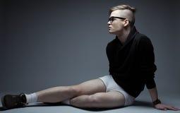Retrato del hombre de moda joven en sentarse de moda de la ropa Foto de archivo