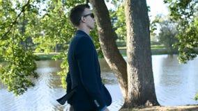 Retrato del hombre de negocios acertado joven que camina de lado hacia entrevista de trabajo o que hace frente a concepto metrajes