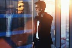 Retrato del hombre de negocios acertado que habla en el teléfono móvil mientras que se opone a ventana en vestíbulo del interior  imágenes de archivo libres de regalías