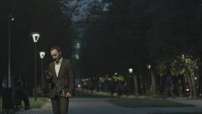Retrato del hombre de negocios adulto hermoso que envía un mensaje de texto mientras que se coloca en la calle de la ciudad, lect Foto de archivo