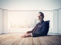 Retrato del hombre de negocios adulto que lleva el traje de moda y que sienta el desván moderno en la silla de cuero contra la ve Imagen de archivo libre de regalías