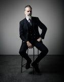 Retrato del hombre de negocios adulto que lleva el traje de moda y que sienta el estudio en silla contra la pared vacía vertical Imágenes de archivo libres de regalías
