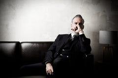 Retrato del hombre de negocios adulto que lleva el traje de moda y que sienta el estudio moderno en el sofá de cuero contra el ho Imagen de archivo libre de regalías