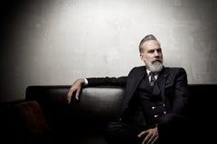 Retrato del hombre de negocios adulto que lleva el traje de moda y que sienta el estudio moderno en el sofá de cuero contra el ho Imagen de archivo