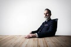 Retrato del hombre de negocios adulto que lleva el traje de moda y que sienta el estudio moderno en la silla de cuero contra el h Foto de archivo libre de regalías