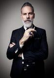 Retrato del hombre de negocios adulto que lleva el traje de moda y que sostiene el cigarrillo contra la pared vacía vertical Imagen de archivo libre de regalías