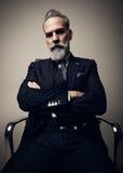 Retrato del hombre de negocios adulto serio que lleva el traje de moda y que se sienta con los brazos cruzados en estudio en sill Imagen de archivo libre de regalías