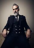Retrato del hombre de negocios adulto serio que lleva el traje de moda y que sienta el estudio en silla contra la pared vacía ver Imágenes de archivo libres de regalías