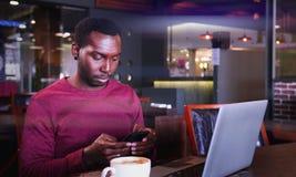 Retrato del hombre de negocios africano feliz que se sienta en un café y que trabaja en el ordenador portátil Imagen de archivo
