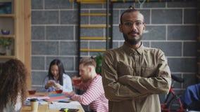 Retrato del hombre de negocios afroamericano joven en camisa y vidrios que sonríe y que mira la cámara mientras que sus colegas almacen de metraje de vídeo