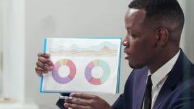 Retrato del hombre de negocios afroamericano que rinde cuentas anuales metrajes