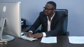 Retrato del hombre de negocios afroamericano serio joven que trabaja con el ordenador port?til y el documento almacen de video